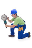 Worker using power tool. Kneeling on the floor using a grinder - isolated Stock Image