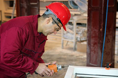Worker Using Power Tool in Workshop. PVC windows and doors manufacturing Stock Photo