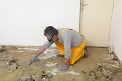 Worker using putty knife for cleaning floor Royalty Free Stock Photo