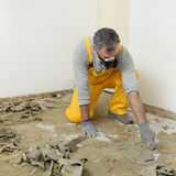 Worker using putty knife for cleaning floor Stock Image