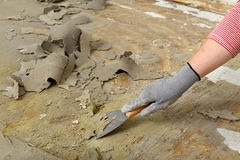 Worker using putty knife for cleaning floor Royalty Free Stock Images