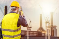 Worker is using radio and crane site during sunset. Construction Royalty Free Stock Photos
