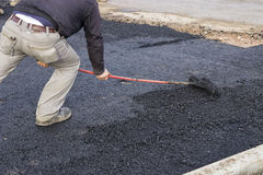 Worker using rake to level asphalt pavement 4 Royalty Free Stock Photo