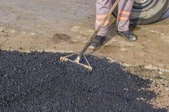 Worker using rake to level asphalt pavement Stock Photo