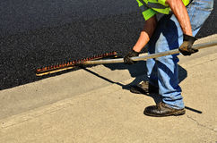 Worker using a rake to push excess asphalt Royalty Free Stock Images
