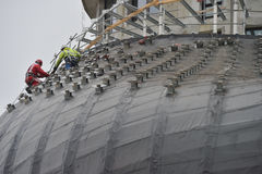 Worker using safety strap on the roof of a bulding under constru Stock Photos