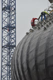 Worker using safety strap on the roof of a bulding under constru Stock Photography