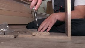 Worker using screwdriver on furniture detail. In room stock video
