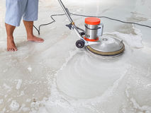 Worker using scrubber machine for cleaning and polishing floor. In bare foots royalty free stock images