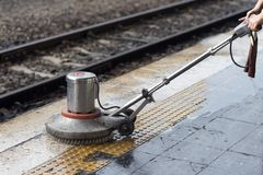 Worker using scrubber machine for cleaning and polishing floor. Cleaning maintenance train at railway station.  stock photos