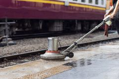 Worker using scrubber machine for cleaning and polishing floor. Cleaning maintenance train at railway station.  stock image
