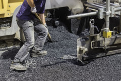 Worker using shovel and spread asphalt to ensure maximum coverag. E. Selective focus and some motion blur present Stock Photos