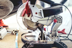 Worker using a sliding compound mitre saw with circular blade for cutting metal and aluminium. Man, worker using a sliding compound mitre saw with circular blade Royalty Free Stock Images