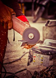 Worker using a small grinder for cutting metal Royalty Free Stock Image