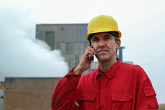 Worker Using Smart Phone With Factory in the Background royalty free stock image