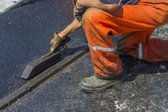 Worker using a special tool to spread mastic asphalt Royalty Free Stock Photo