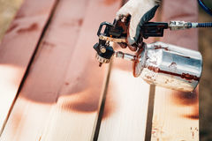 Worker using spray gun for applying brown paint over timber. Male worker using spray gun for applying brown paint over timber Royalty Free Stock Photography