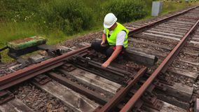 Worker using tablet PC on railway track. In summer day stock footage