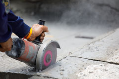 Worker using tool to cut concrete floor with blank space on right. Worker using tool to cut concrete floor Royalty Free Stock Photo