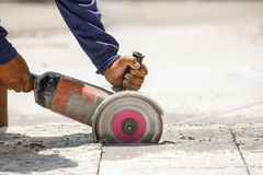 Worker using tool to cut concrete floor with blank space on right Royalty Free Stock Photography