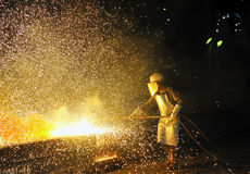 Worker using torch cutter to cut through metal Stock Photography