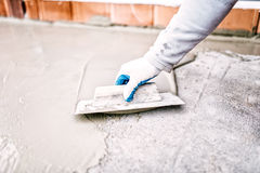 Worker using trowel and mason's float for hydroisolating and waterproofing house Stock Image