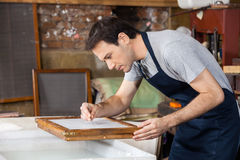 Worker Using Tweezers To Clean Paper In Factory Stock Photography