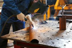 Worker using welding equipment for metalworking. In shop Stock Photo