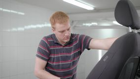 Worker is vacuuming removed black car seat in a room of auto-service during cleaning, car washing. Worker is vacuuming removed black car seat in a room of auto stock video