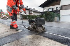 Worker at asphalting with vibrator. Worker with vibrating plate during asphalting work on sidewalk Royalty Free Stock Image