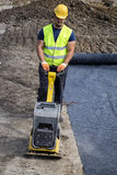 Worker with vibrating plate compactor. BELGRADE, SERBIA - SEPTEMBER 09, 2016: Worker with vibrating plate compactor in action, compact soil to create a dense and Stock Photo