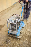 Worker with vibrating plate compactor machine. At sand ground compaction Stock Photo