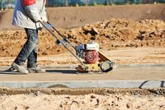 Worker with vibration compactor. Builder worker at sand ground compaction with vibration plate compactor machine before pavement roadwork Royalty Free Stock Photos