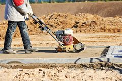 Worker with vibration compactor. Builder worker at sand ground compaction with vibration plate compactor machine before pavement roadwork Stock Photos