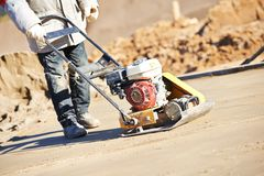 Worker with vibration compactor. Builder worker at sand ground compaction with vibration plate compactor machine before pavement roadwork Stock Images