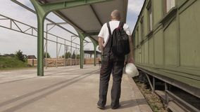 Worker waiting near vagons at station stock video footage