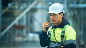 Worker with walkie talkie and safety equipment on oil plant.