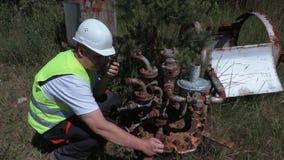 Worker on walkie talkie turn off old gas crane stock video footage