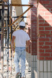 Worker Walking Away. Construction worker walking away under scaffolding at construction site Royalty Free Stock Images