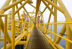 The offshore oil rig. The worker is walking cross the pathway bridge of offshore oil rig Stock Photo