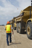 Worker Walking Near Trucks At Landfill Site Stock Image