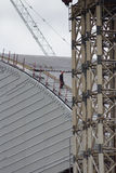 A worker walks down the new containment shelter at Chernob. Chernobyl Nuclear Power Plant/Ukraine - 25 May 2013: A worker carefully descends the arching slope of royalty free stock images