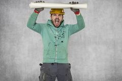 The worker wants to destroy the construction plans. Protective helmet on the head Royalty Free Stock Image