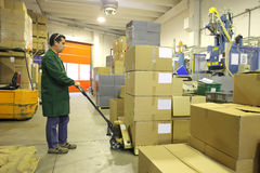 Worker in warehouse. Worker with fork lifter in the warehouse Royalty Free Stock Photos