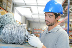 Worker in warehouse checking barbed wire Stock Photography