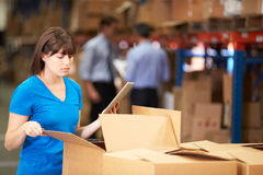 Worker In Warehouse Checking Boxes Using Digital Tablet. Looking away from camera Royalty Free Stock Images