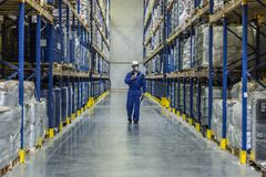 Worker of warehouse with chemistry goods. Walking among racks Royalty Free Stock Image