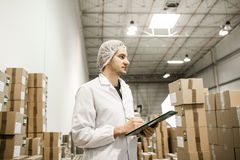 Worker In warehouse for food packaging. Manager writing on clipboard in automated production line at modern factory. Color toned image Royalty Free Stock Photography