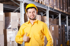 Worker in warehouse. Happy young male worker in yellow uniform in warehouse Royalty Free Stock Image
