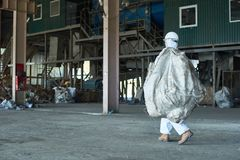 Worker in warehouse of recycling factory. Full length portrait of men in hazmat suit carrying bag of recyclable materials in warehouse of waste processing plant Stock Photo